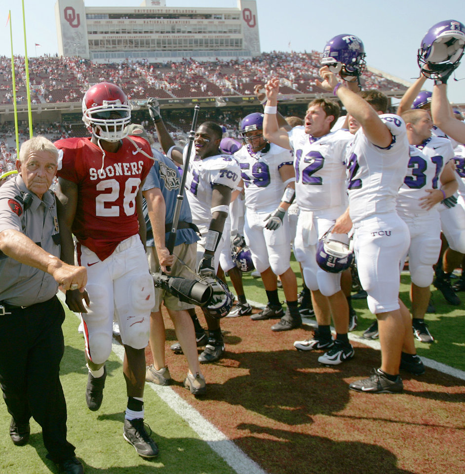 Photo - Adrian Peterson, left, walks past TCU players as they celebrate their 17-10 victory over OU in 2005.  Photo By Bryan Terry, The Oklahoman Archive