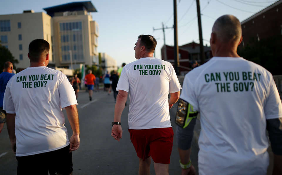 Photo - Gov. Kevin Stitt walks up the Walnut Street during Oklahoma City Memorial Marathon in Oklahoma City, Sunday, April 28, 2019. [Sarah Phipps/The Oklahoman]
