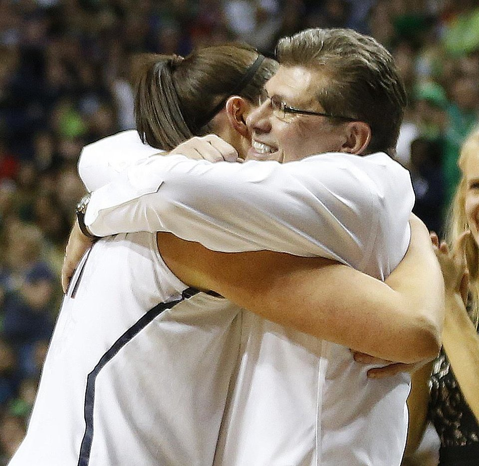 Photo - Connecticut center Stefanie Dolson (31) embraces Connecticut head coach Geno Auriemma during the second half of the championship game against Notre Dame in the Final Four of the NCAA women's college basketball tournament, Tuesday, April 8, 2014, in Nashville, Tenn. Connecticut won 79-58. (AP Photo/John Bazemore)