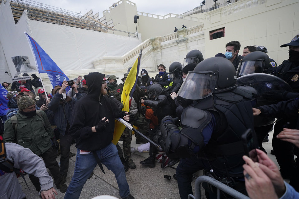 Photo - Trump supporters try to break through a police barrier, Wednesday, Jan. 6, 2021, at the Capitol in Washington. As Congress prepares to affirm President-elect Joe Biden's victory, thousands of people have gathered to show their support for President Donald Trump and his claims of election fraud. (AP Photo/Julio Cortez)