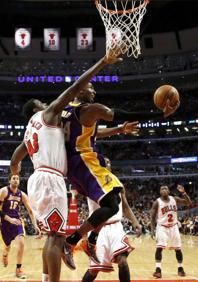 Photo - Los Angeles Lakers guard Kobe Bryant, right, shoots a reverse lay up past Chicago Bulls center Nazr Mohammed (48) during the second half of an NBA basketball game Monday, Jan. 21, 2013, in Chicago. The Bulls won 95-83. (AP Photo/Charles Rex Arbogast)