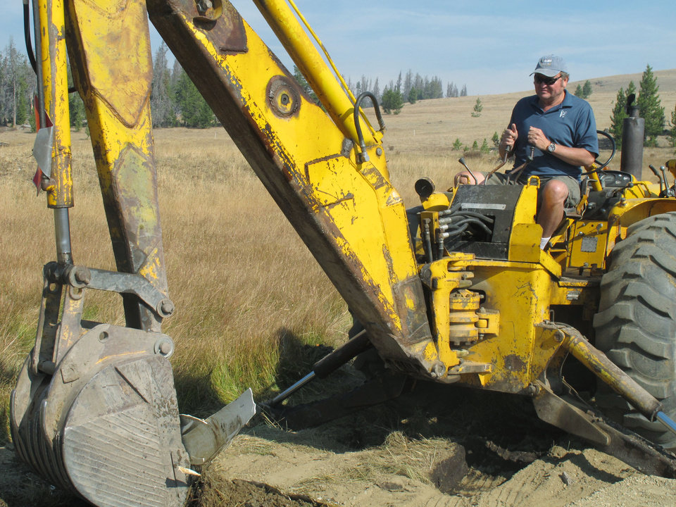In this Sept. 19, 2012 photo, Montana Gov. Brian Schweitzer operates a backhoe as he clears a stream under a bridge he built on his ranch in Marysville, Mont., about 45 miles from the capitol in Helena. A day spent with Schweitzer riding four-wheelers and talking politics makes it easy to understand why he's one of the most unusual, and most effective, governors in the country. It's not often that a governor from a rural state with no major media market within 700 miles is considered potential cabinet level or even presidential material. But Schweitzer, 57, is creating that kind of dark horse buzz with a skillfully employed mastery of current affairs and a unique capacity for shameless and entertaining self-promotion.(AP photo/Matt Gouras)