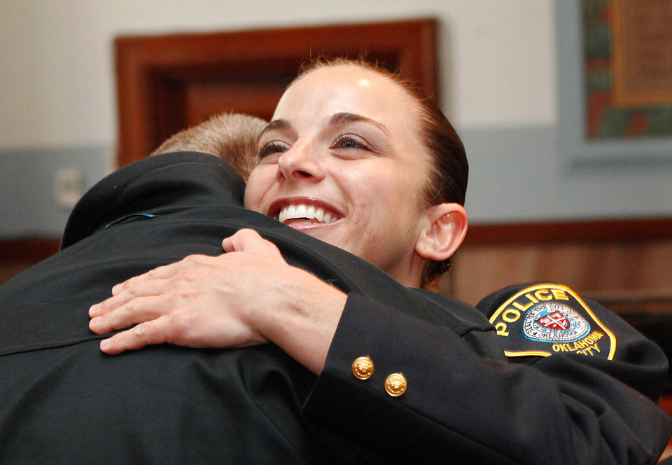 Photo - Officer Katie Lawson hugs another officer as she is greeted by the nearly 40 fellow officers who remained in the courtroom after her shooters were sentenced. Brothers Alex Mercado and Hector Escalante were given separate sentences by District Judge Donald Deason in an Oklahoma County courtroom Tuesday afternoon, Nov. 8, 2011 for  their involvement in shooting Oklahoma City police officer Katie Lawson during an ambush in south Oklahoma City in Aug, 2010.   Chief Bill Citty and his four assistant chiefs were seated among  nearly 40 uniformed police officers in the courtroom as the sentences were imposed. Several said they came to support Officer Lawson.  Photo by Jim Beckel, The Oklahoman