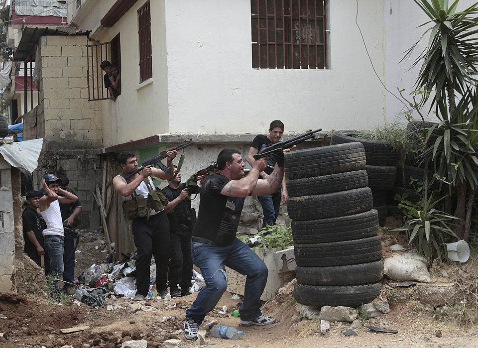 Photo -   Sunni gunmen fire during clashes, in the northern port city of Tripoli, Lebanon, Sunday May 13, 2012. Gunfire broke out in the city Saturday and continued through the night primarily between a neighborhood populated by Sunni Muslims who hate Syrian President Bashar Assad and another area with many Assad backers from his Alawite sect. Lebanon's national news agency NNA said one soldier was shot dead by a sniper in the city early Sunday. Another man was found dead on the side of a road while a third died after a shell landed in a residential neighborhood. (AP Photo/Hussein Malla)