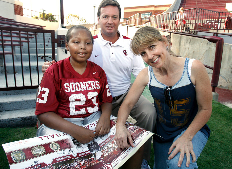 Photo - OU COLLEGE FOOTBALL: Head coach Bob Stoops poses with David Haywood, 12, and Oklahoma Children's Cancer Association volunteer Kay Tangner during Media Day for the University of Oklahoma football team at Gaylord Family -- Oklahoma Memorial Stadium in Norman, Oklahoma on Wednesday, August 6, 2008.   BY STEVE SISNEY, THE OKLAHOMAN    ORG XMIT: KOD