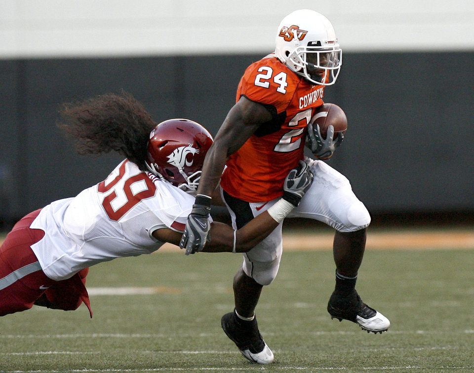 Photo - OSU's Kendall Hunter (24) breaks free from WSU's Sekope Kaufusi (59) during the college football game between the Washington State Cougars (WSU) and the Oklahoma State Cowboys (OSU) at Boone Pickens Stadium in Stillwater, Okla., Saturday, September 4, 2010. Photo by Sarah Phipps, The Oklahoman
