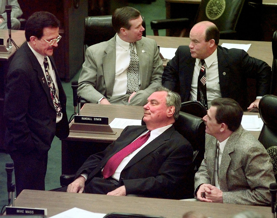 Legislators from the House and Senate visit while waiting for Gov. Keating to enter the House Chambers to deliver his state of the state address to a joint session at the state capitol Monday afternoon.  Seated at desk in front is Sen. Gene Stipe and Rep. Mike Mass.  Standing is Rep. Al Lindley.  Seated at back desk is Rep. Randall Erwin and Sen. Frank Shurden.