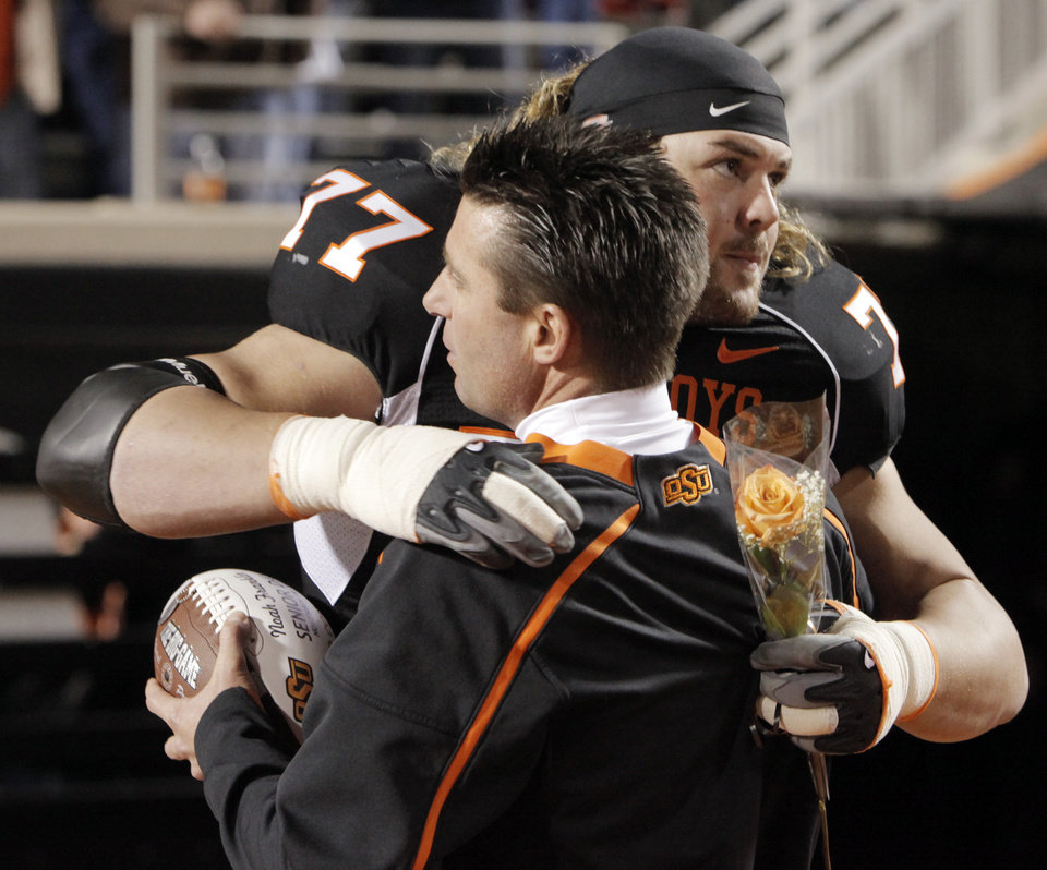 Photo - OSU's Noah Franklin (77) hugs head coach Mike Gundy as Franklin is recognized for senior night at the college football game between Oklahoma State University (OSU) and the University of Colorado (CU) at Boone Pickens Stadium in Stillwater, Okla., Thursday, Nov. 19, 2009. Photo by Nate Billings, The Oklahoman