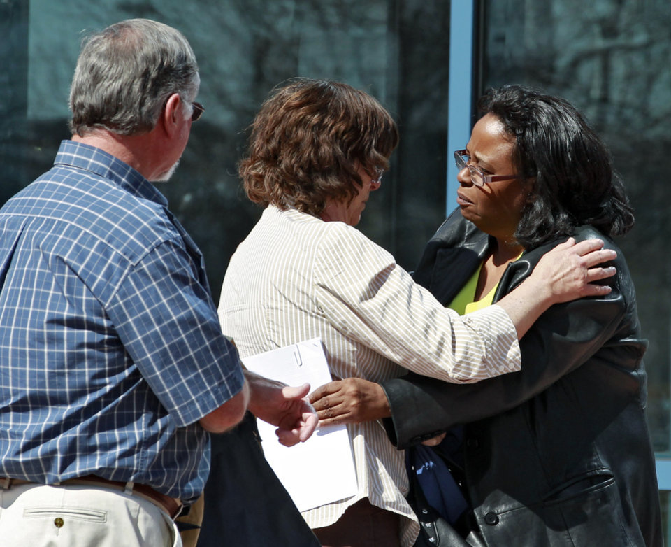 Sherry Delaney, right, hugs Arlene Holmes, center, as Robert Holmes, left, looks on as they leave the courthouse in Centennial, Colo., on Monday, April 1, 2013, after attending hearings in the case against their son Aurora theater shooting suspect James Holmes. The prosecution announced they would seek the death penalty against Holmes. (AP Photo/Brennan Linsley)