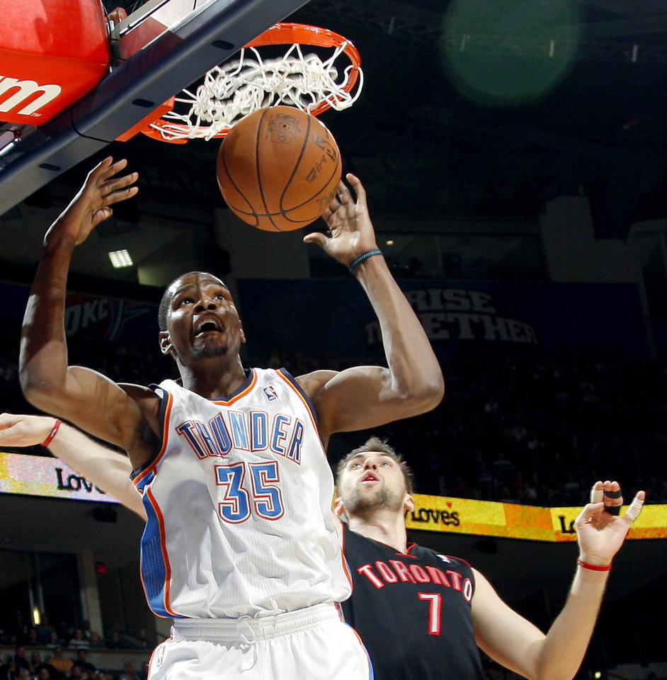 Photo - Oklahoma City's Kevin Durant slams the ball in front of Toronto's Andrea Bargnani during their NBA basketball game at the OKC Arena in downtown Oklahoma City on Sunday, March 20, 2011. Photo by John Clanton, The Oklahoman