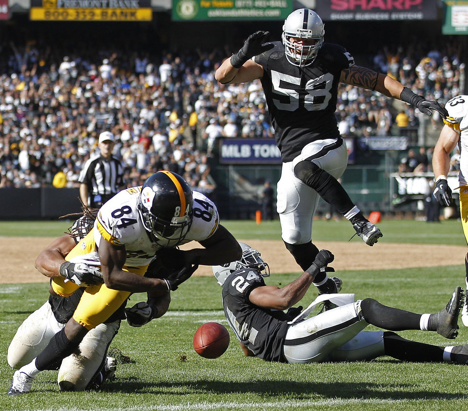Photo -   Pittsburgh Steelers wide receiver Antonio Brown (84) fumbles the ball near the goal line while being brought down by Oakland Raiders linebacker Philip Wheeler during the third quarter of an NFL football game in Oakland, Calif., Sunday, Sept. 23, 2012. An unnecessary roughness penalty against the Raiders was called on the play giving the Steelers a touchdown. In the background are Raiders defensive end Dave Tollefson (58) and free safety Michael Huff (24). (AP Photo/Tony Avelar)