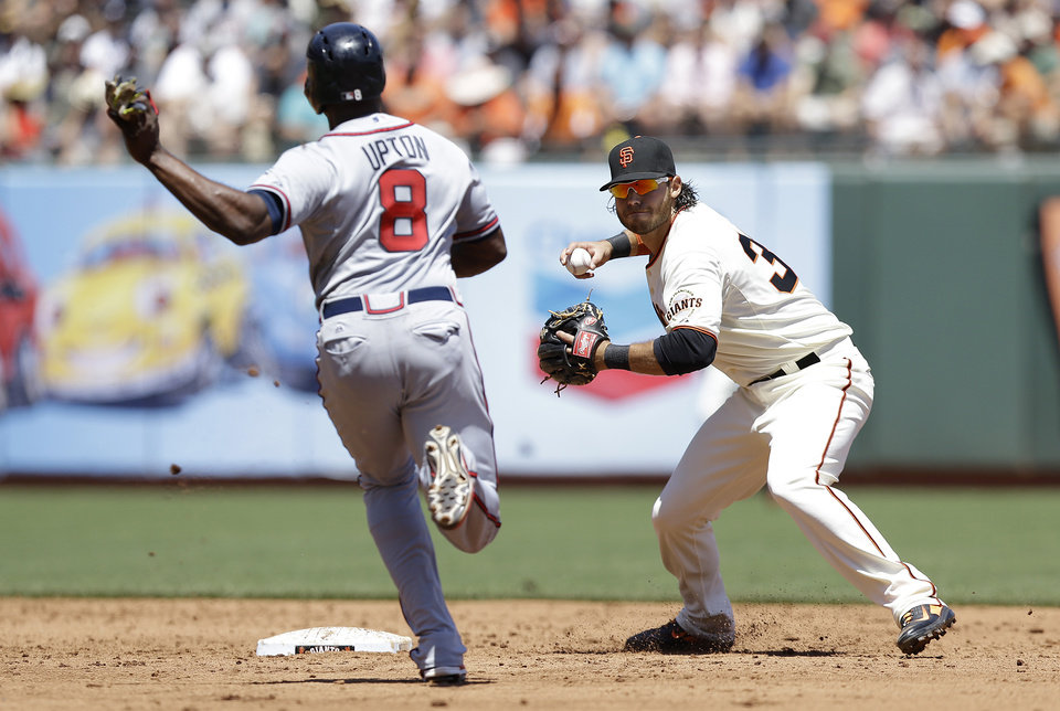 Photo - San Francisco Giants shortstop Brandon Crawford, right, throws to first base after forcing out Atlanta Braves' Justin Upton (8) at second on a double play hit into by Freddie Freeman during the third inning of a baseball game in San Francisco, Wednesday, May 14, 2014. (AP Photo)