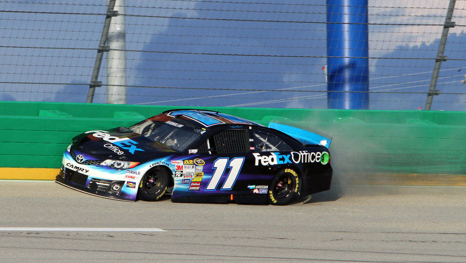 Photo - Denny Hamlin (11) hit the outside wall in between Turns 3 and 4 during the NASCAR Sprint Cup series auto race Saturday, June  28, 2014, at Kentucky Speedway in Sparta, Ky. The crash put him out of the race. (AP Photo/Garry Jones)