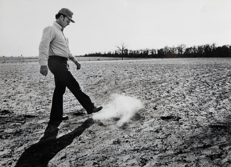 Photo - Arthur Rickets is shown kicking up dirt as he walks through a dry peanut field after the 1980 drought. STAFF PHOTO BY J. DON COOK, THE OKLAHOMAN