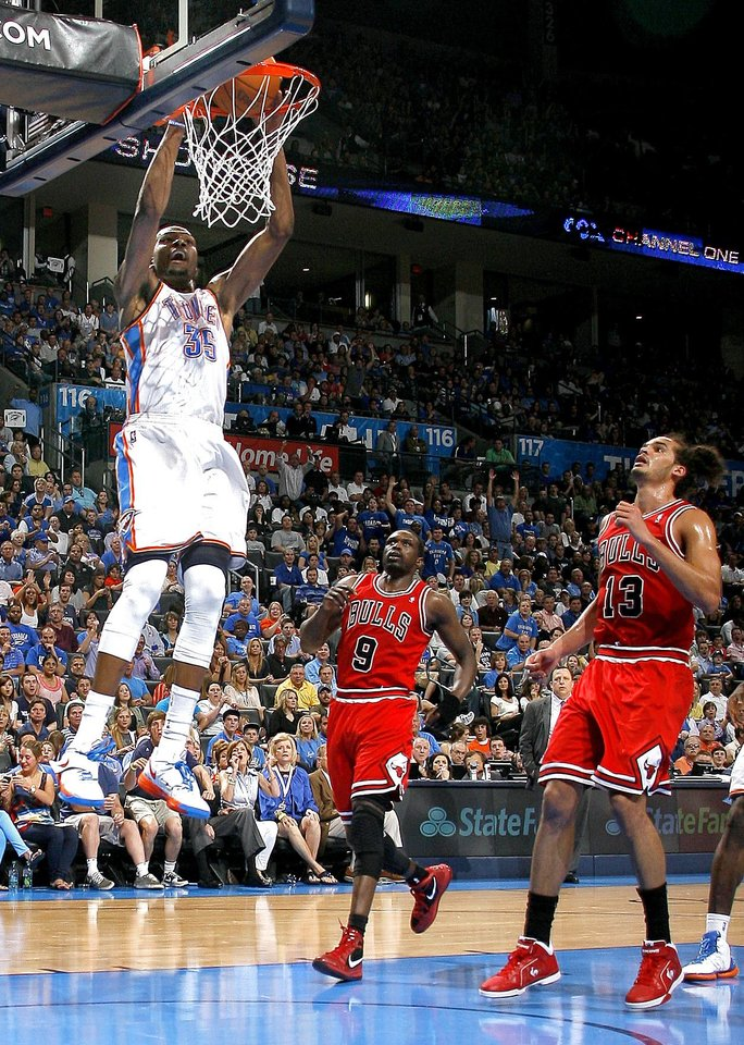 Photo - Oklahoma City's Kevin Durant (35) dunks in front of Chicago's Luol Deng (9) and Joakim Noah (13) during the NBA basketball game between the Chicago Bulls and the Oklahoma City Thunder at Chesapeake Energy Arena in Oklahoma City, Sunday, April 1, 2012. Photo by Sarah Phipps, The Oklahoman