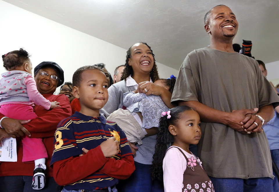 Deric and Amanda Isaac with their children participate in a ceremony marking their welcome home after extensive repairs through Central Oklahoma Habitat for Humanity's Veteran Critical Home Repair project. The Home Depot Foundation and Parker Brothers Roofing contributed. <strong>Jim Beckel - THE OKLAHOMAN</strong>