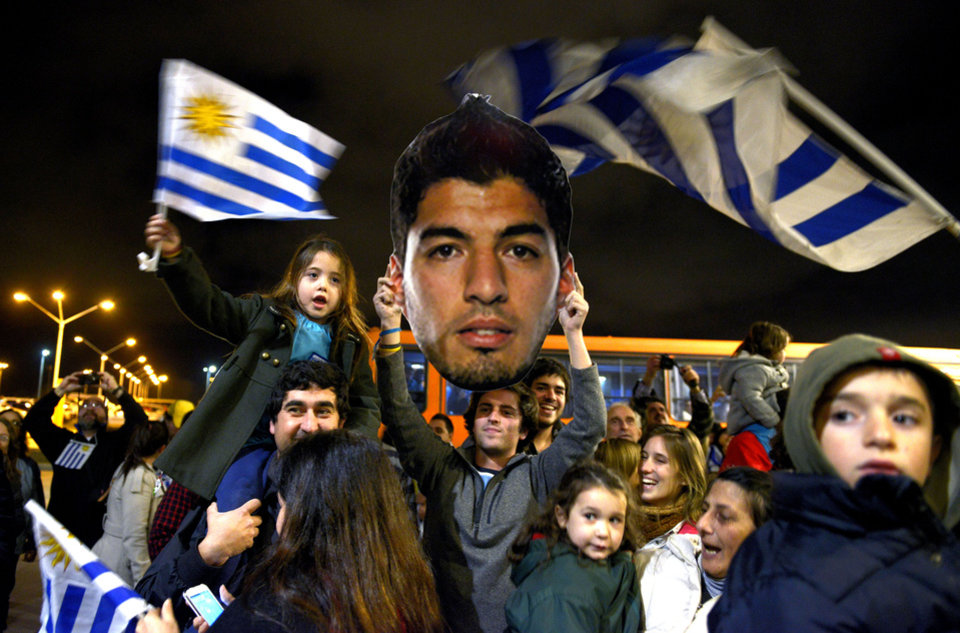 Fans of Uruguay's national soccer team await the arrival of Uruguay player Luis Suarez at Carrasco International Airport in the outskirts of Montevideo, Uruguay, Thursday, June 26, 2014. The Uruguay forward, widely regarded as one of the best players in the world, was banned by FIFA from all football for four months on Thursday for biting an Italian opponent in an incident that marred the team's victory and progression to the second round. (AP Photo/Matilde Campodonico)