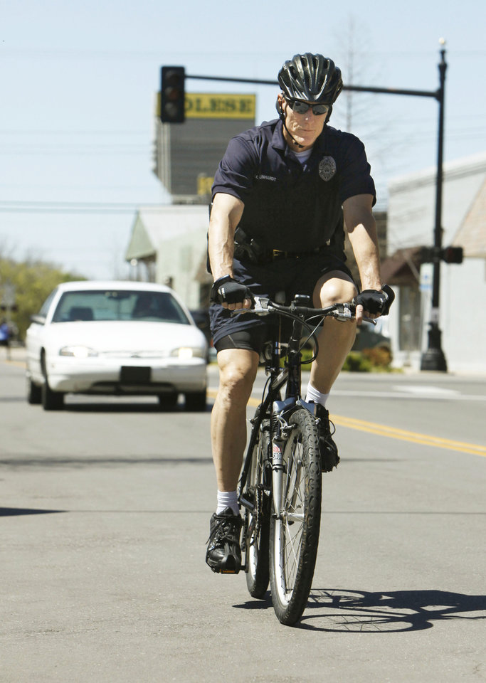 Photo - Edmond police Lt. Chuck Linhardt rides his bicycle through  downtown Edmond.