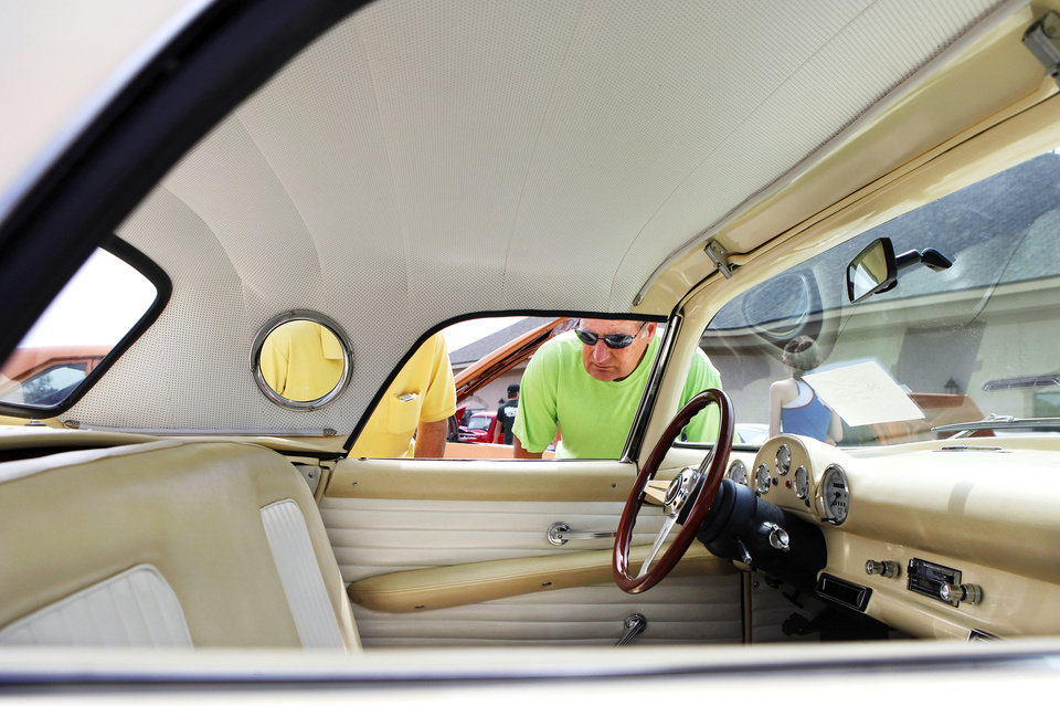 A man leans down to look inside this Ford Thunderbird at the Bethany 66 Festival in a parking lot in the city's downtown area Saturday,  May 26,  2012,  Photo by Jim Beckel, The Oklahoman