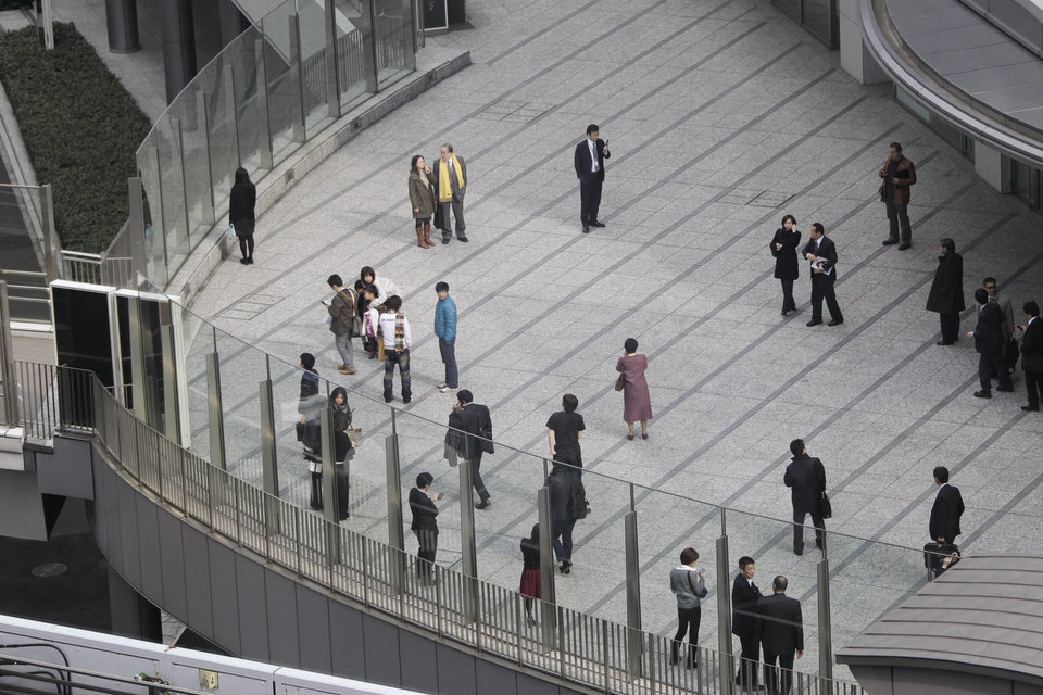 Photo - Office workers in Tokyo's Shiodome district near Tokyo Bay stay on the pedestrian deck Friday, March 11, 2011, shortly after a  7.9-magnitude earthquake has struck off Japan's northeastern coast. (AP Photo/Koji Sasahara)