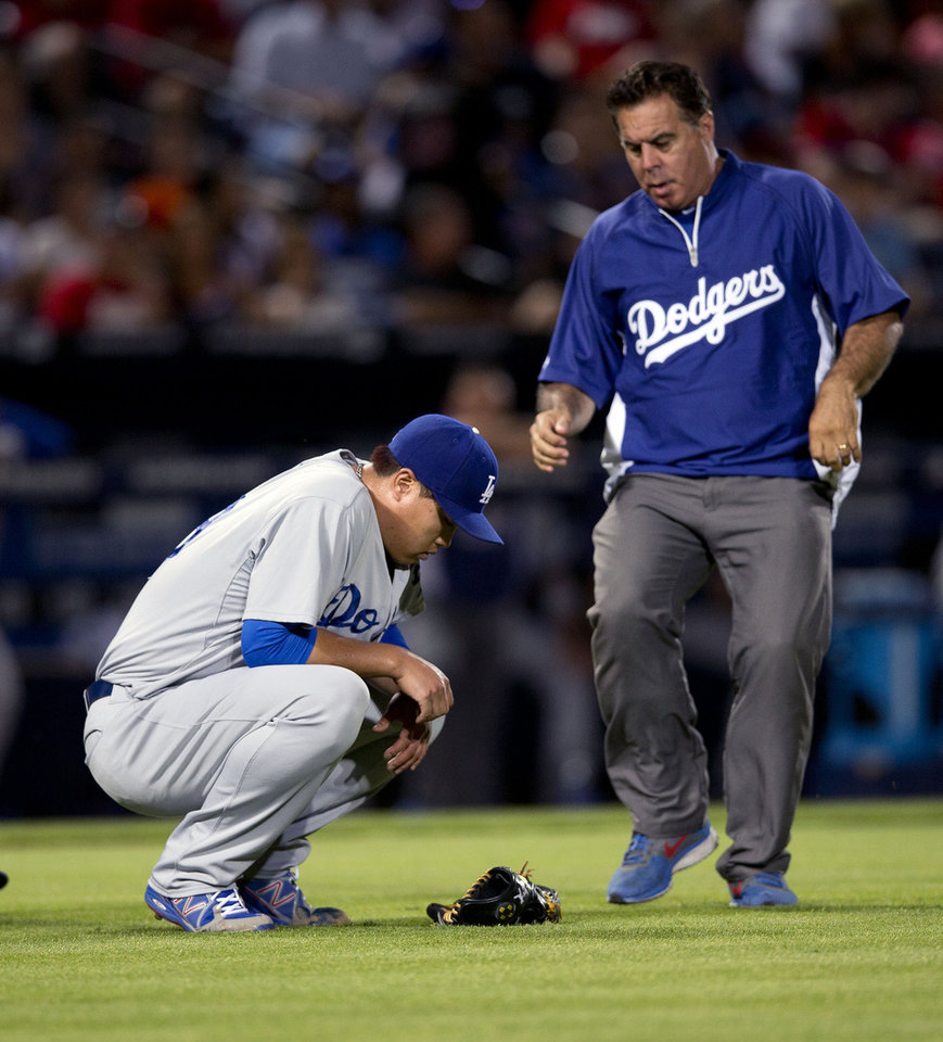 Photo - A member of the Los Angeles Dodgers training staff runs onto the field to help injured starting pitcher Hyun-Jin Ryu (99) in the sixth inning of a baseball game against the Atlanta Braves Wednesday, Aug. 13, 2014, in Atlanta. Ryu left the game under his own power. (AP Photo/John Bazemore)