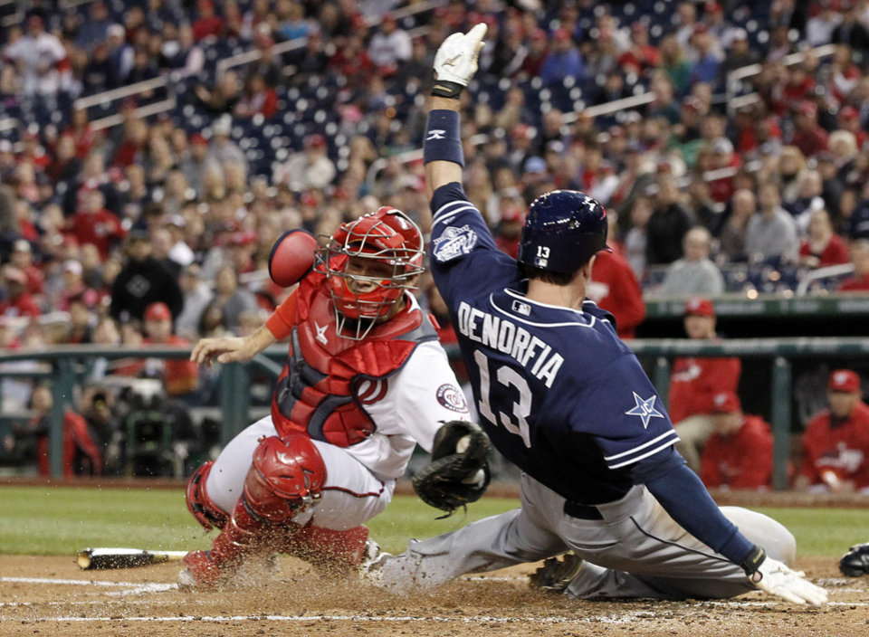 Photo - Washington Nationals catcher Jose Lobaton, left, is late with the tag on San Diego Padres' Chris Denorfia who is safe at home on a double hit by Seth Smith, during the fourth inning of a baseball game at Nationals Park, Thursday, April 24, 2014, in Washington. (AP Photo/Alex Brandon)