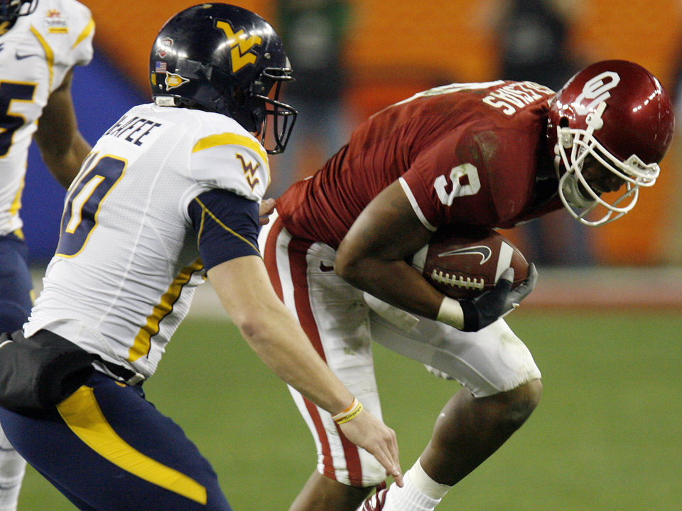 Photo - Oklahoma's Juaquin Iglesias (9) tries to get past West Virginia's Pat McAfee (40) during the second half of the Fiesta Bowl college football game between the University of Oklahoma Sooners (OU) and the West Virginia University Mountaineers (WVU) at The University of Phoenix Stadium on Wednesday, Jan. 2, 2008, in Glendale, Ariz. 