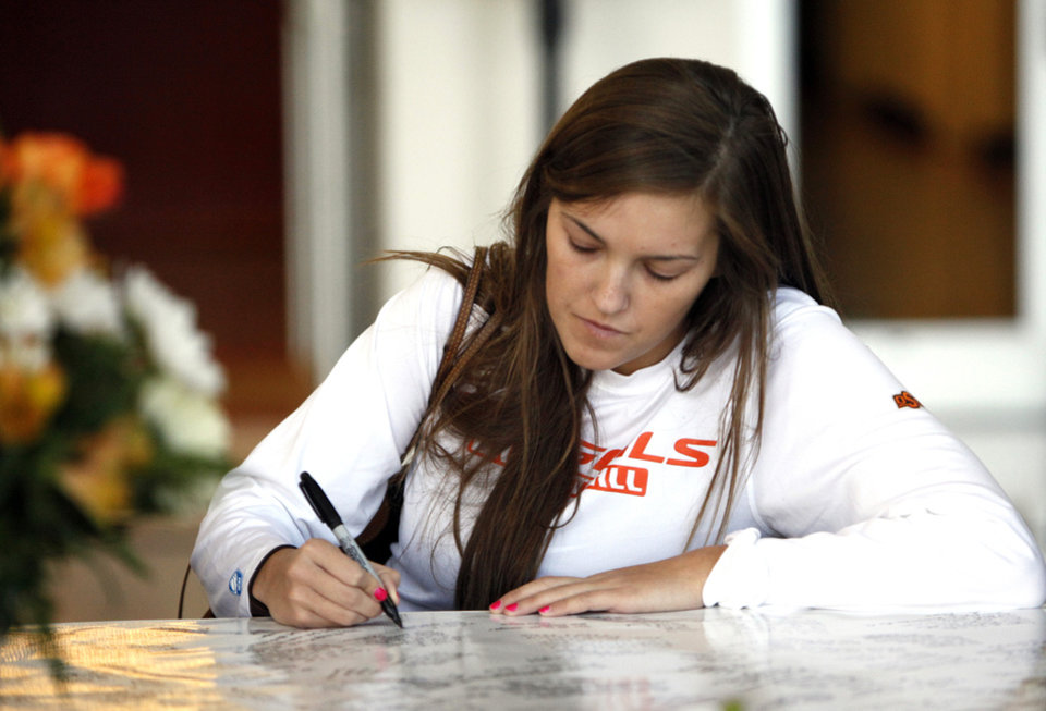 Oklahoma State basketball player Taylor Schippers signs a memorial banner for  OSU women's head coach Kurt Budke and assistant coach Miranda Serna at Gallagher- Iba Arena in Stillwater, Okla.,  Friday, Nov. 18, 2011.  Photo by Sarah Phipps, The Oklahoman