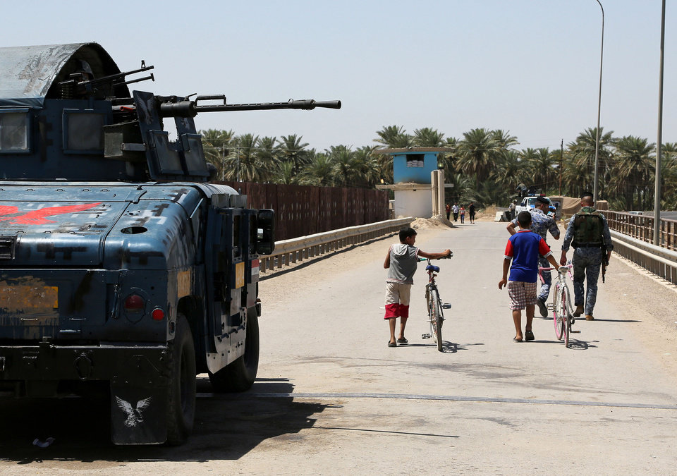 Photo - Iraqi federal police patrol as local children push their bikes in the town of Taji, about 12 miles (20 kilometers) north of Baghdad, Iraq, Thursday, June 26, 2014. The Islamic State of Iraq and the Levant (ISIL) took over the country's second largest city 10 days ago. U.S. Secretary of State John Kerry warned Mideast nations on Wednesday against taking new military action in Iraq that might heighten already-tense sectarian divisions, as reports surfaced that Syria launched airstrikes across the border and Iran has been flying surveillance drones over the neighboring country. (AP Photo/Karim Kadim)