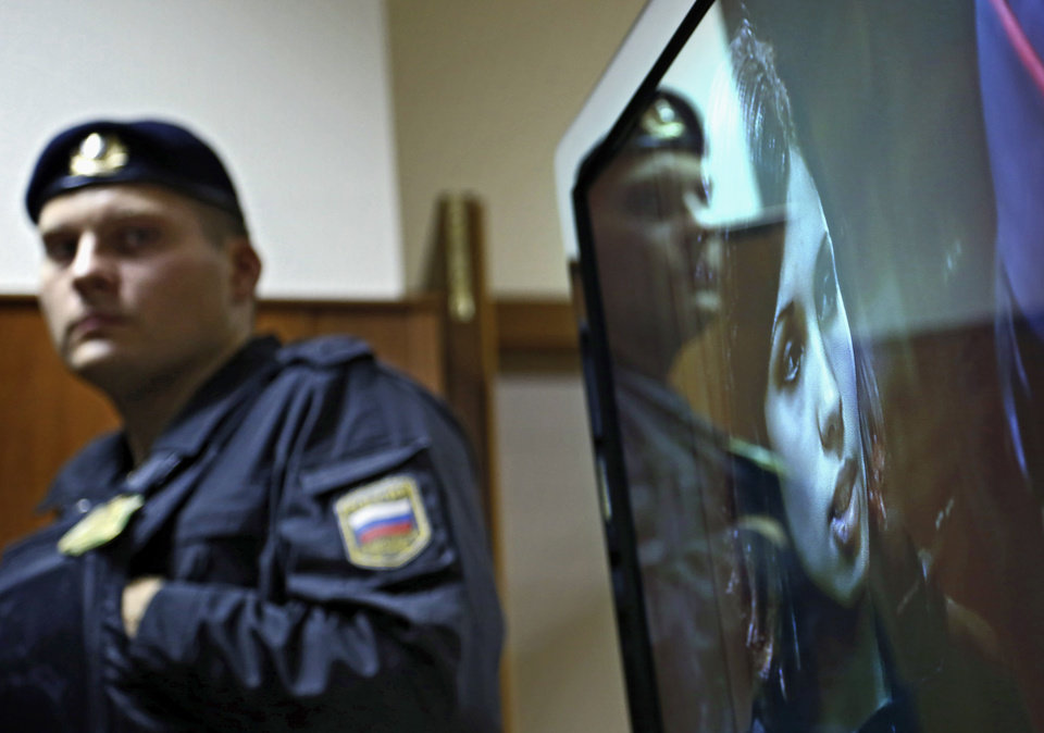 A policeman stands, as band member Nadezhda Tolokonnikova speaks on a TV screen in a hall outside a court room of the Moscow City Court where three members of the punk band Pussy Riot are set to make their case before a Russian appeals court that they should not be imprisoned, in Moscow, Wednesday. Oct. 10, 2012. Their impromptu performance inside Moscow's main cathedral in February came shortly before Putin was elected to a third term. The three women were convicted in August of hooliganism motivated by religious hatred and sentenced to two years in prison. (AP Photo/Sergey Ponomarev)