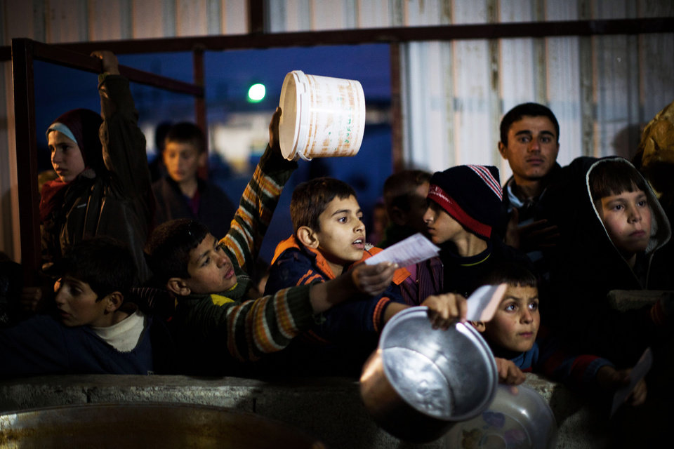 Syrian children wait in line for food distribution at a refugee camp near the Turkish border, in Azaz, Syria, Sunday, Dec. 9, 2012. (AP Photo/Manu Brabo)