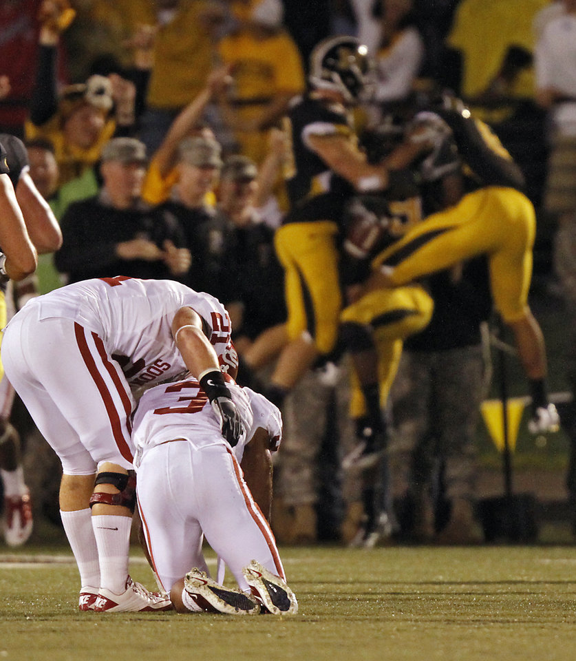 Photo - Oklahoma's Tom Wort (21) helps Jonathan Nelson (3) off the field as Missouri celebrates a touchdown during the second half of the college football game between the University of Oklahoma Sooners (OU) and the University of Missouri Tigers (MU) on Saturday, Oct. 23, 2010, in Columbia, Mo. Oklahoma lost the game 36-27. Photo by Chris Landsberger, The Oklahoman