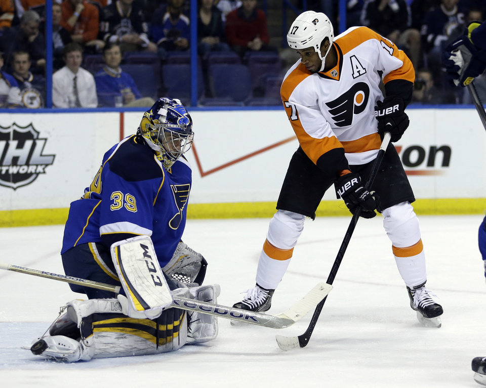 Photo - Philadelphia Flyers' Wayne Simmonds, right, watches as St. Louis Blues goalie Ryan Miller deflects a puck during the first period of an NHL hockey game Tuesday, April 1, 2014, in St. Louis. (AP Photo/Jeff Roberson)