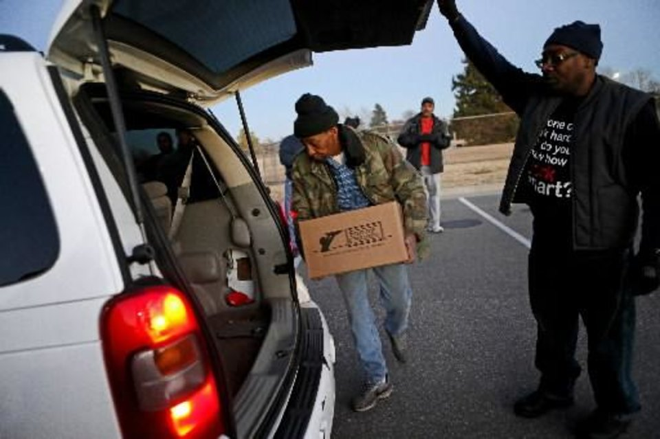 Feed the Children volunteer Wayne Richmond, at right, helps volunteer John Hunter loads a 25-pound box of food into a car outside of Douglass High School in Oklahoma City, Tuesday, Dec. 11, 2012. Photo by Bryan Terry