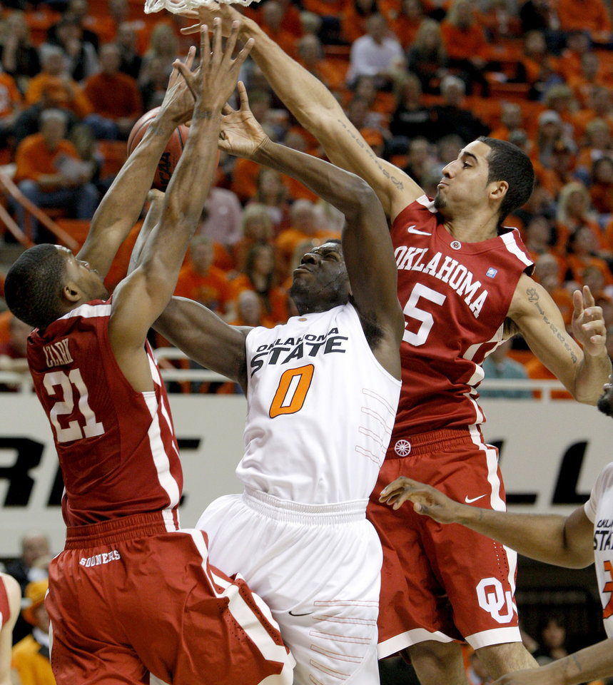 Photo - Oklahoma State's Jean-Paul Olukemi (0) goes to the basket between Oklahoma's Cameron Clark (21) and C.J. Washington (5) during the Bedlam men's college basketball game between the University of Oklahoma Sooners and Oklahoma State University Cowboys at Gallagher-Iba Arena in Stillwater, Okla., Saturday, February, 5, 2011. Photo by Bryan Terry, The Oklahoman