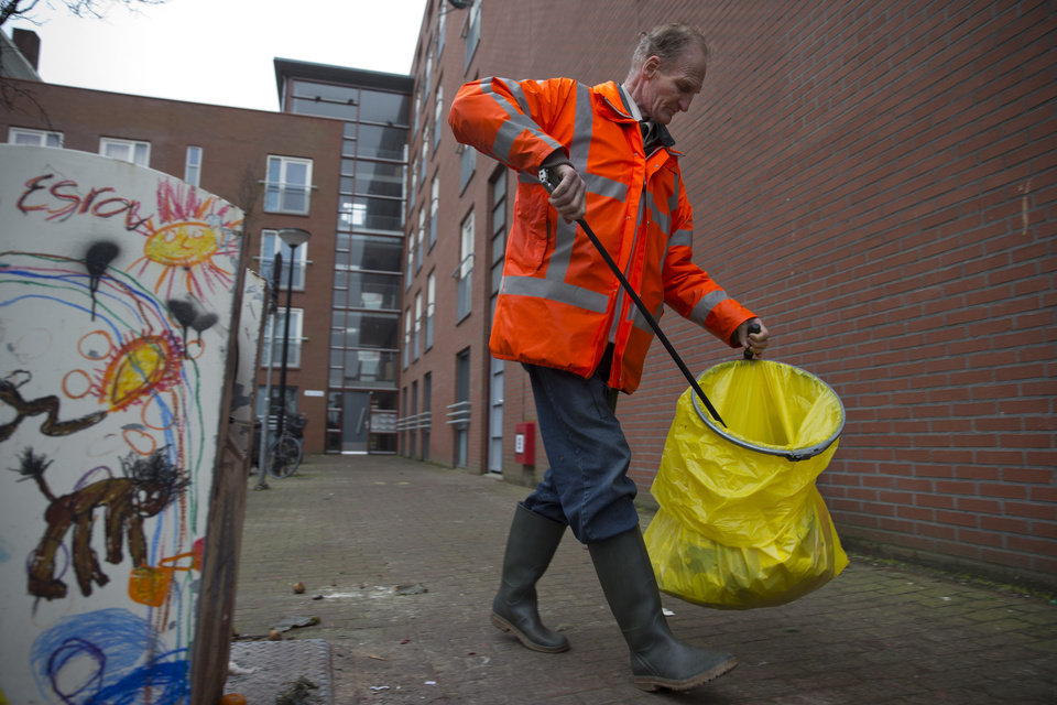 Photo - Fred Schiphorst, an alcoholic and former construction worker, sets out on his daily route to collect litter in Amsterdam's eastern part Wednesday Jan. 15, 2014. In a pilot project that has drawn attention in the Netherlands and around the world, the city has teamed up with a charity organization in hopes of improving the neighborhood and possibly improving life for the alcoholics. Not by trying to cure them, but instead by offering to fund their drinking outright. That is, participants are given beer in exchange for a little work collecting litter, eating a decent meal, and sticking to their schedule. (AP Photo/Peter Dejong)