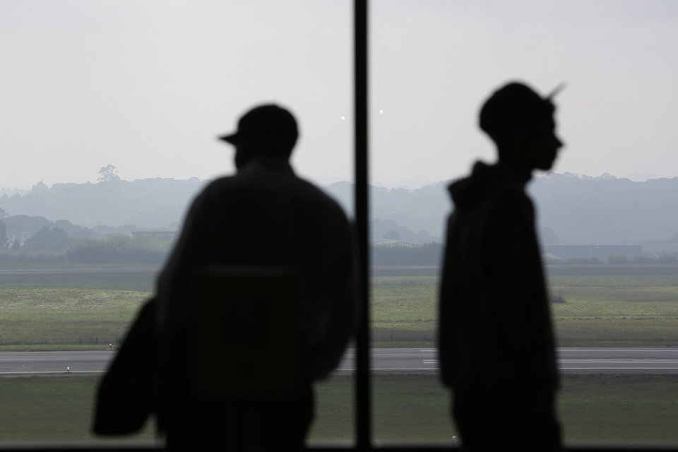 Photo - Waiting passengers are silhouetted against a window in an airport terminal, where flights were delayed due to heavy fog, in World Cup host city Curitiba, Brazil, Tuesday, June 17, 2014.  (AP Photo/Jon Super)