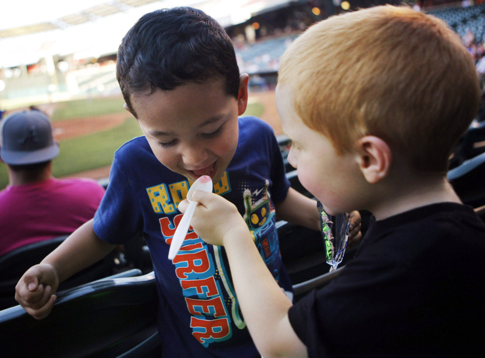 Three-year-old Colt Morris feeds his cousin, four-year-old Eli Cavazos, a frozen lemonade during a minor league baseball game between the Oklahoma City Redhawks and the Iowa Cubs on a hot night at Chickasaw Bricktown Ballpark in Oklahoma City on June 10, 2013. Photo by KT KING, The Oklahoman