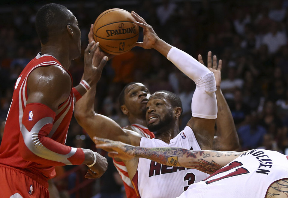 Photo - Houston Rockets' Dwight Howard (left) and Terrenc Jones (6) force Miami Heat's Dwyane Wade (3) to pass the ball during the first half of an NBA  basketball game in Miami, Sunday, March 16, 2014. (AP Photo/J Pat Carter)