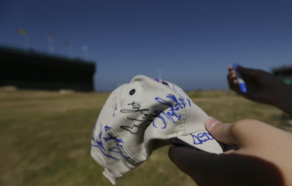 A golf fan holds out a pen and a cap to be signed by golfers as they come off the 18th green during the third round of the British Open Golf Championship at Muirfield, Scotland, Saturday July 20, 2013. (AP Photo/Jon Super)