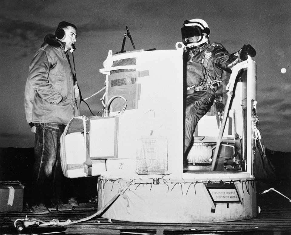 FILE - In this Nov. 16, 1959, file photo, provided by the U.S. Air Force, Capt. Joseph Kittinger Jr., aerospace laboratory test director, sits in the open balloon gondola after his first parachute test jump for Project Excelsior at Holloman Air Force Base in Alamogordo, N.M. The gondola carried him at an altitude of 76,400 feet for his record free fall jump of more than 12 miles. At left is David Willard, who designed and developed special equipment for the gondola. On Tuesday, Oct. 9, 2012, if winds allow, in the desert surrounding Roswell, N.M., pilot Felix Baumgartner will attempt to break Kittinger\'s world record for the highest and fastest free fall. (AP Photo/U.S. Air Force, File)