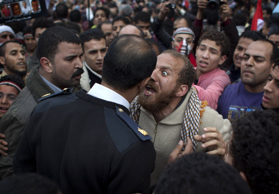 FILE - In this Sunday, Feb. 13, 2011 file photo, an Egyptian protester, center right, argues with a police officer in Tahrir Square in downtown Cairo, Egypt. A government inquiry into the deaths of nearly 900 protesters during Egypt's uprising has concluded police were behind nearly all the killings and used snipers on rooftops overlooking Tahrir Square to shoot into the huge crowds. The report, parts of which were obtained by The Associated Press, is the most authoritative account of the killings and determines the deadly force used could only have been authorized by ousted President Hosni Mubarak's security chief, with the president's full knowledge. (AP Photo/Emilio Morenatti, File)