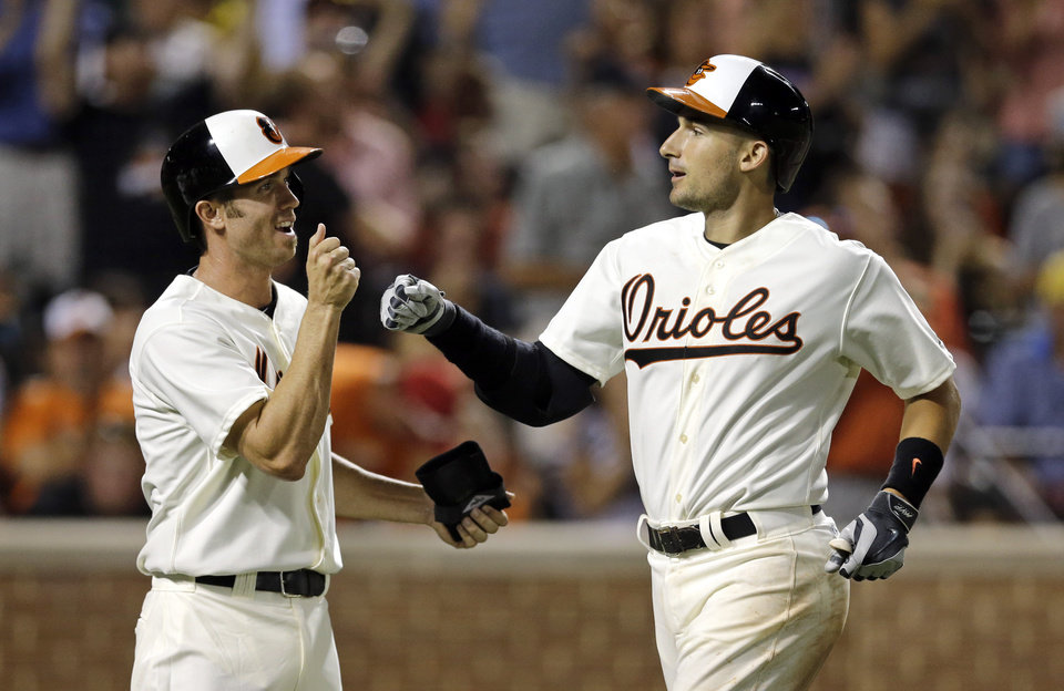 Photo - Baltimore Orioles' J.J. Hardy, left, fist-bumps teammate Ryan Flaherty after scoring on Flaherty's home run in the sixth inning of an interleague baseball game against the St. Louis Cardinals, Friday, Aug. 8, 2014, in Baltimore. Baltimore won 12-2. (AP Photo/Patrick Semansky)