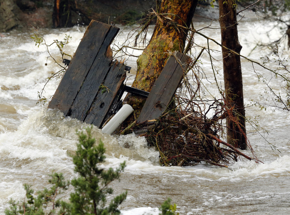 Photo - A broken picnic table is pinned against a tree in rushing waters below Turner Falls park on Thursday, June 18, 2015 in Davis, Okla. Photo by Steve Sisney, The Oklahoman