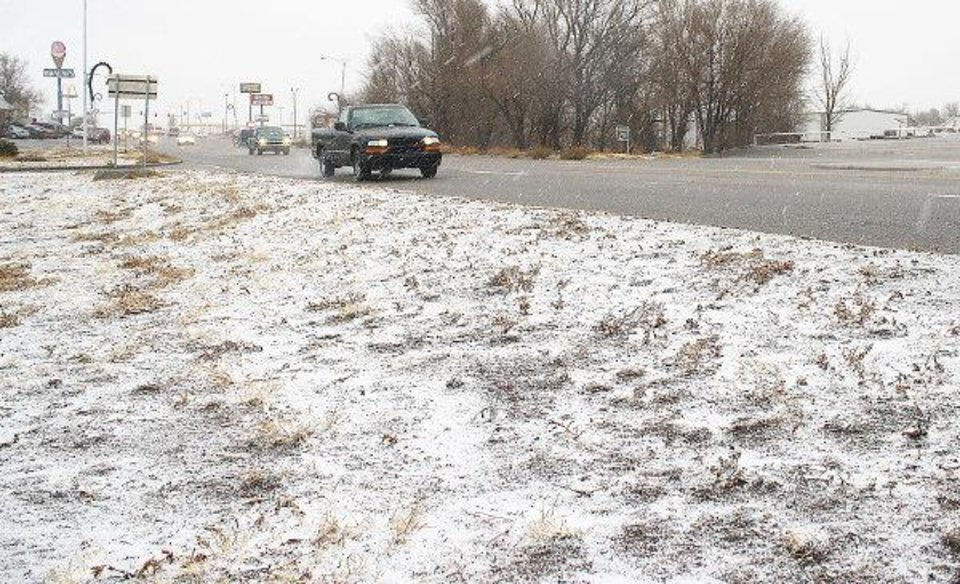 Photo - Traffic makes its way down U.S. 64 Monday as snow and sleet falls in Guymon.   AP Photo/ Shawn Yorks, The Guymon Daily Herald
