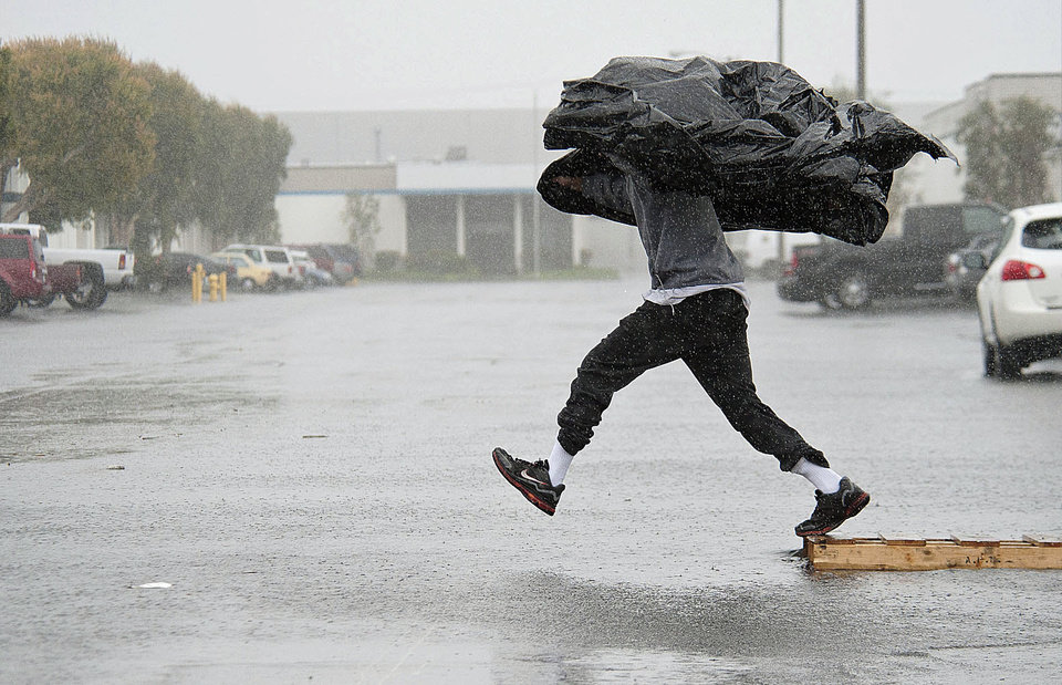 Photo - Manufacturing Assembly worker Terry Young, 24, of Rialto, Calif., uses a sheet of plastic to protect himself from a downpour Friday, Feb. 28, 2014, as he jumps a flooded parking lot from a wood pallet to get to a food truck during his break in Anaheim, Calif. The first wave of a powerful Pacific storm spread rain and snow early Friday through much of California, where communities endangered by a wildfire just weeks ago now faced the threat of mud and debris flows. (AP Photo/The Orange County Register, Ken Steinhardt) MAGS OUT; LOS ANGELES TIMES OUT