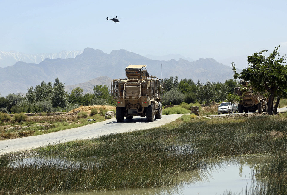 Photo - NATO armored vehicles depart from the site of a suicide attack in the Parwan province of eastern Afghanistan, Tuesday, July 8, 2014. An Afghan official says that at least 16 people, including four Czech soldiers, were killed Tuesday in a suicide attack near a clinic in eastern Afghanistan. A provincial spokesman says the others killed are at least 10 civilians and two police officers. The Taliban claimed responsibility for the attack in a statement sent to the media. The violence came as Afghanistan was mired in an electoral crisis after one of the candidates in the presidential elections, Abdullah Abdullah, refused to accept any results until millions of ballots are audited for fraud. (AP Photo/Rahmat Gul)