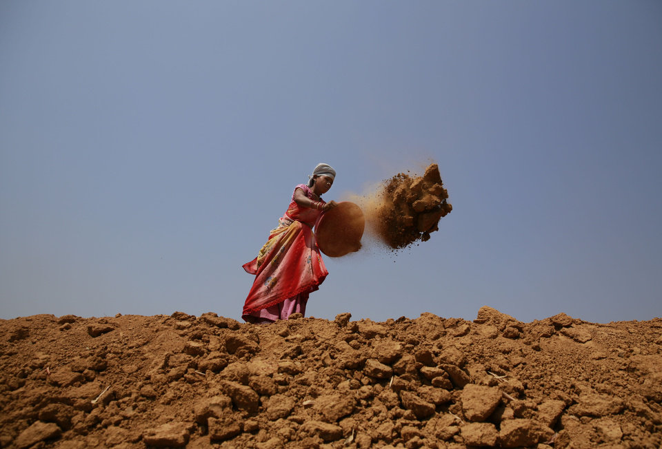 Photo - In this April 15, 2014 photo, Indian woman Shanti Patel helps dig a water reservoir at the edge of an open coal mine in Sarasmal village near the industrial city of Raigarh, in Chhattisgarh state, India. While India's rapid economic growth over the past decade has boosted the incomes and living standards of millions - mostly city-dwellers - the environmental impact has often been ignored and the rural poor have been left behind. (AP Photo/Rafiq Maqbool)
