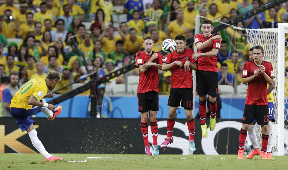 Photo - Brazil's Neymar, left, takes a free kick against Mexico's defensive wall during the group A World Cup soccer match between Brazil and Mexico at the Arena Castelao in Fortaleza, Brazil, Tuesday, June 17, 2014.  (AP Photo/Marcio Jose Sanchez)