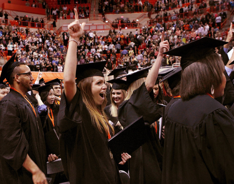 Students celebrate at their seats after being told by OSU President Burns Hargis they officially had been graduated from the university at the conclusion of the graduation ceremony. Undergraduates at OSU participated in the school's 127th commencement ceremony the weekend of Friday, May 3 and Saturday, May 4, 2013 inside Gallagher-Iba Arena on the university's campus.These photos were taken at the Saturday morning ceremony when students from the College of Agricultural Sciences and Natural Resources, and the Spears School of Business were conferred with degrees.   Photo  by Jim Beckel, The Oklahoman.
